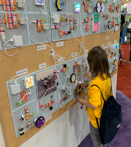 Little girl playing with littleBits invention on a tradeshow booth wall.