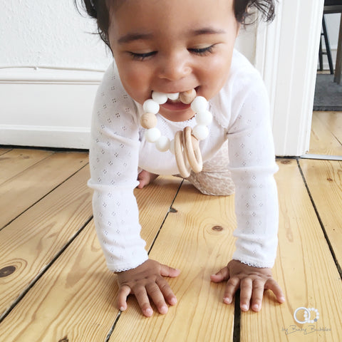Baby crawling with teething rattle in her mouth