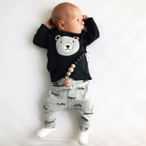 Baby boy wearing black silicone and wood pacifier clip