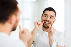 man flossing in mirror