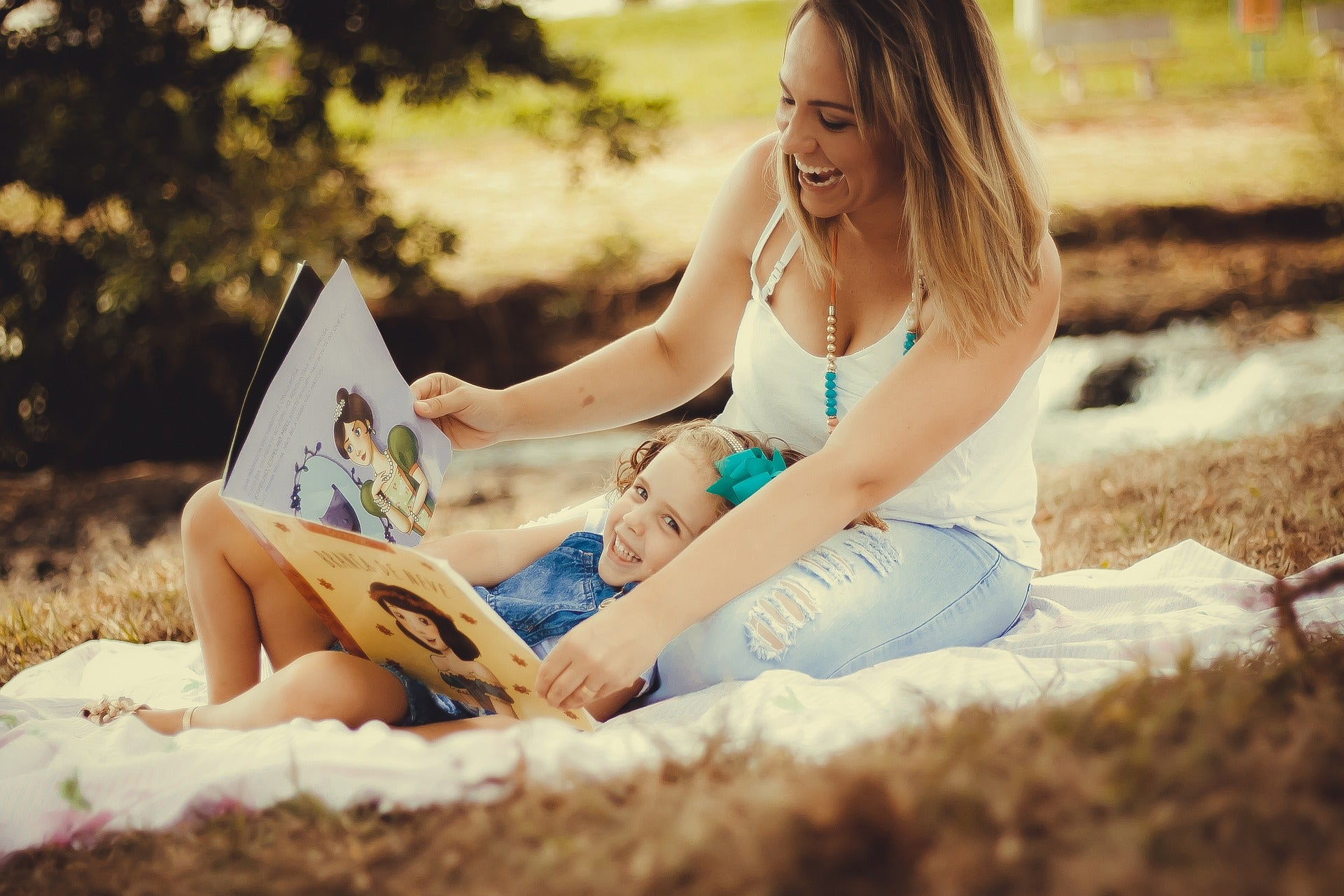 Mother and daughter reading a book on the grass
