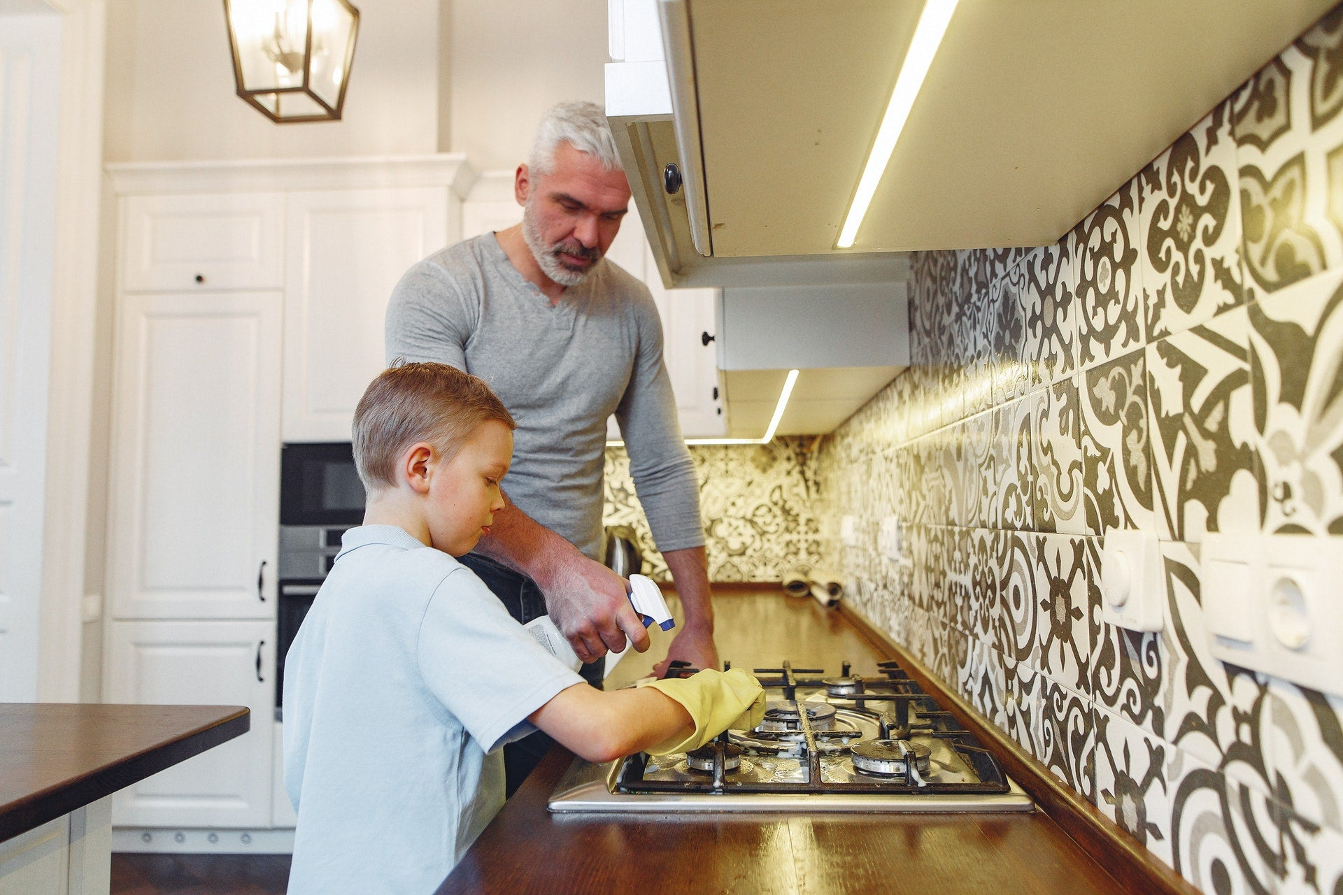 Dad and son cleaning the kitchen