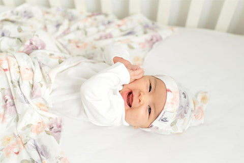 Smiling baby in swaddle blanket