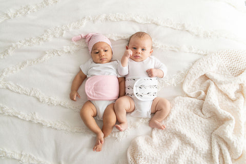 Two babies wearing a belly band and a newborn hat.