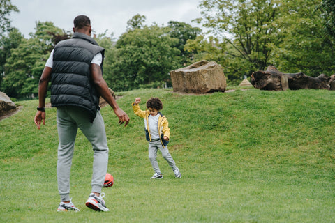 Dad playing soccer with son