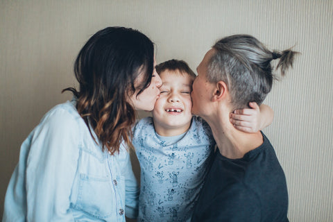 mom and dad kissing child