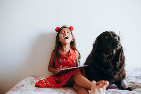 A girl reading with a black dog