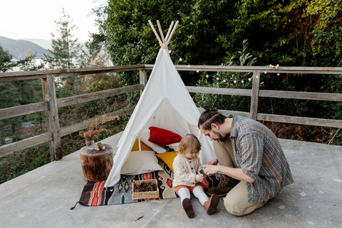 Father and child in a teepee