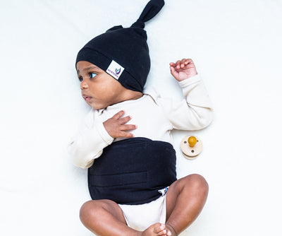 baby on bed wearing noir belly band and top knot hat