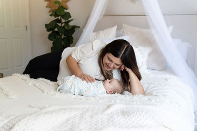 mom and baby on bed with baby swaddled in luna swaddle