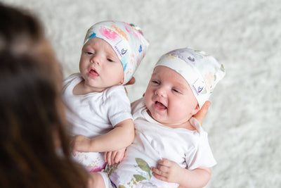 mom holding two smiling babies wearing memeeno organic cotton belly bands and hats