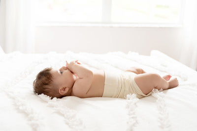 baby wearing naturelle unbleached cotton bloomer laying on the bed and eating fingers