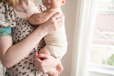 mom holding baby wearing naturelle unbleached cotton bloomer