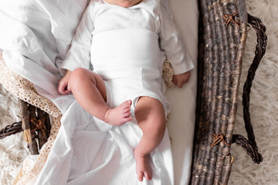 body shot of baby in basket in white organic cotton memeeno baby belly bloomer
