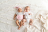 two babies on bed wearing memeeno organic cotton baby belly bands, one in pink and one in feathers print