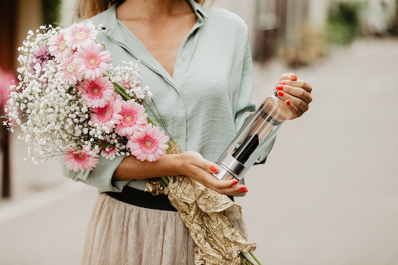 lady holding flowers and a crystal infusion water bottle by rock your water Manipura