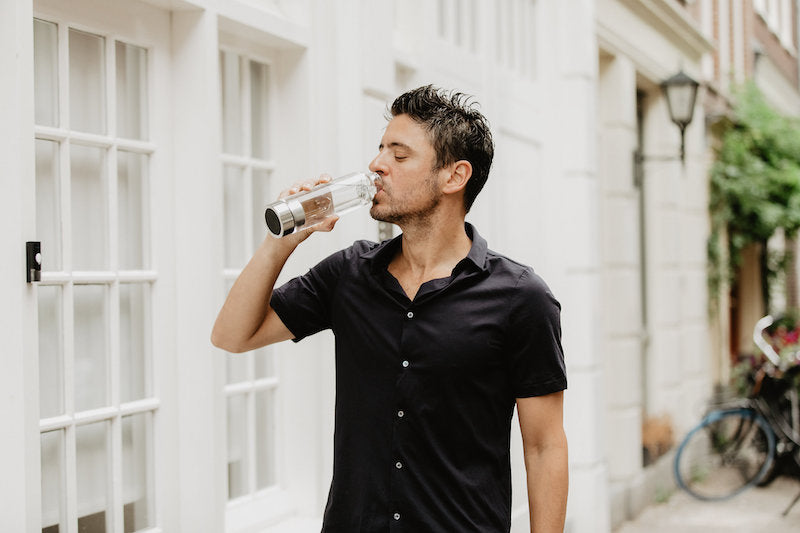 A man drinking from a Crystal Infusion water bottle by rock your water manipura