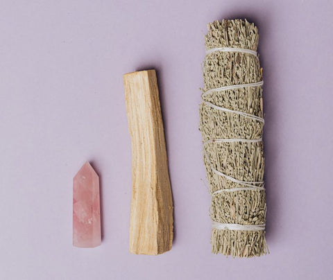 photo of sage and palo santo beside a rose quartz crystal