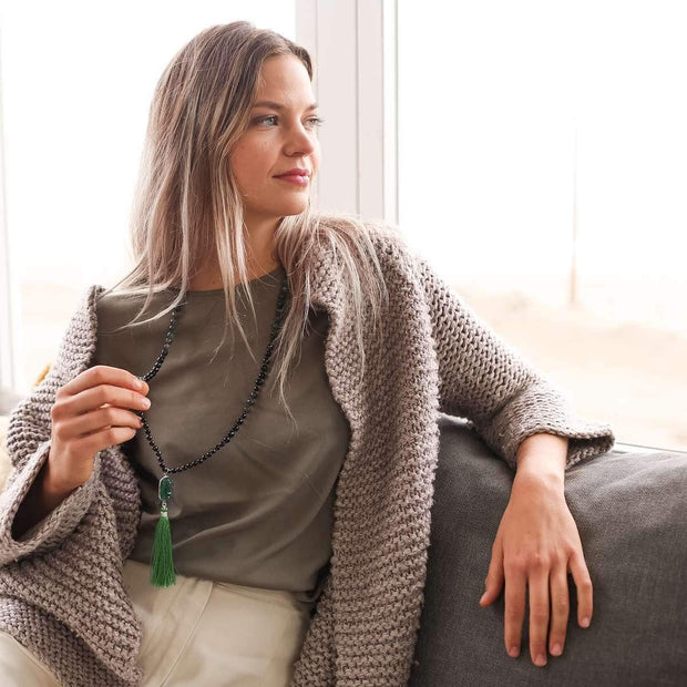 Lady relaxed on the couch holding in her hand Green Gemstone Mala, Manipura - Handmade in Amsterdam