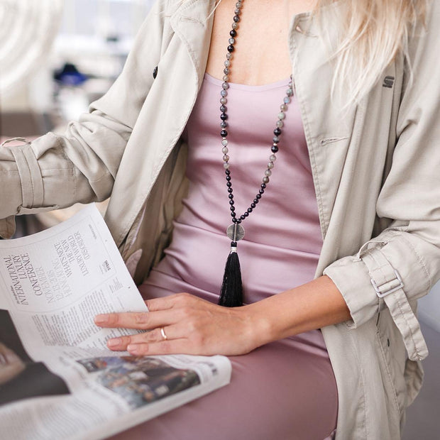 Lady reading a newspaper wearing Black and Grey Gemstone Mala, Manipura - Handmade in Amsterdam