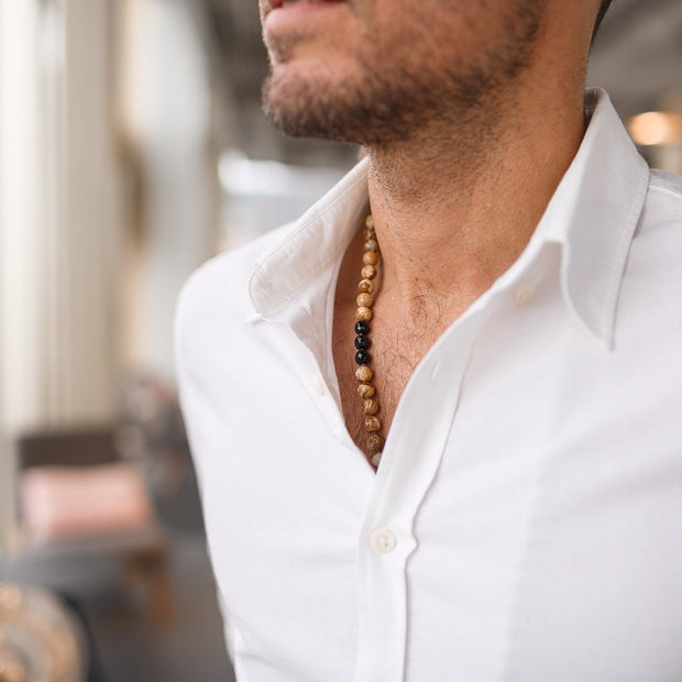 Man in white shirt wearing Jasper and Onyx Gemstone Mala, Manipura - Handmade in Amsterdam