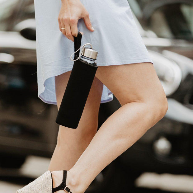 A lady walking in the street with a crystal water bottle in a black neoprene sleeve by Manipura