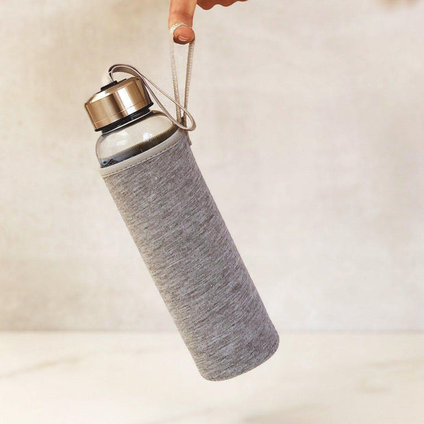 A finger holding a crystal water bottle in a Grey Neoprene Sleeve by Manipura Rock Your Water