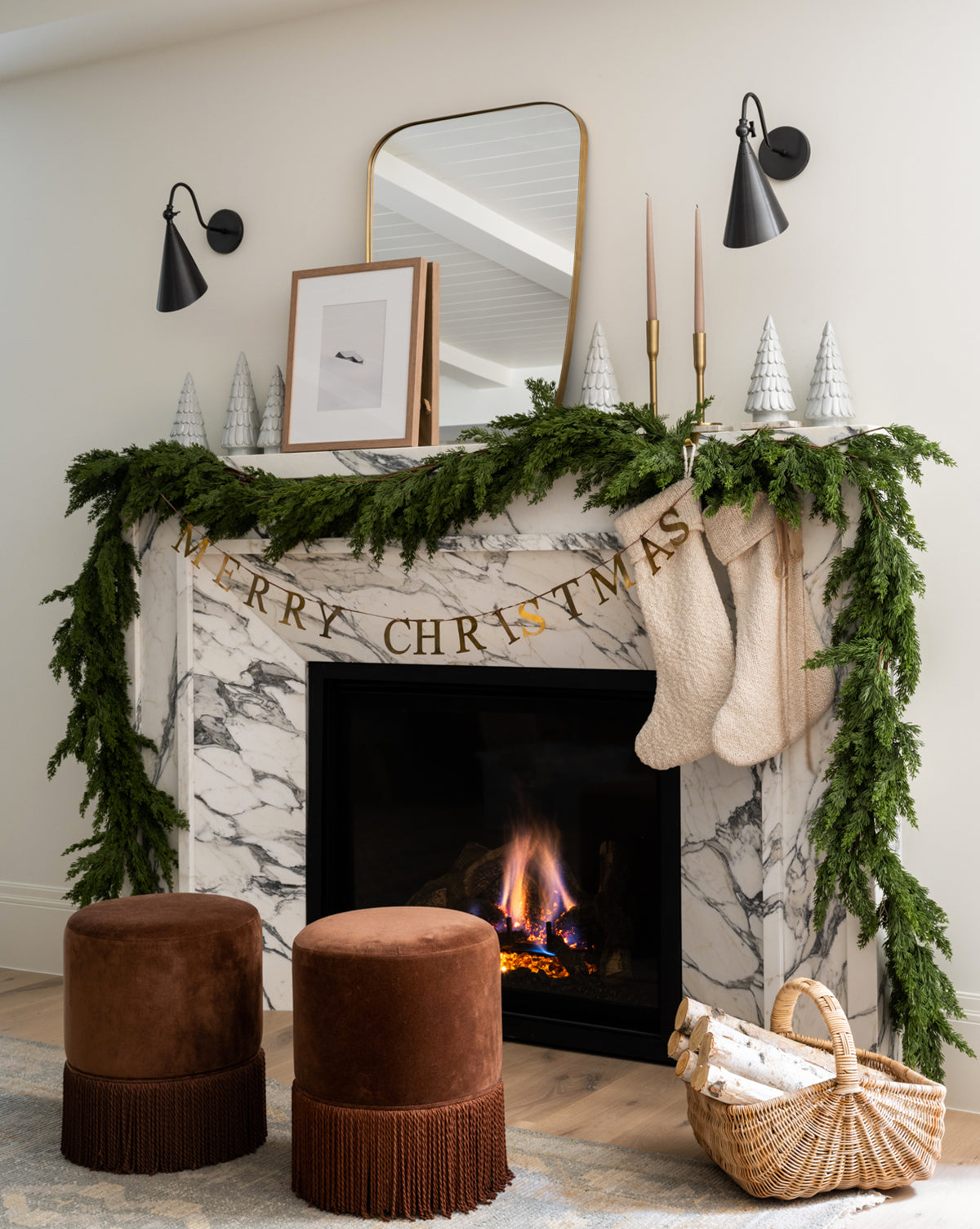 French country style Christmas mantel with garland, white stockings, banner, and basket of birch logs - McGee & Co.