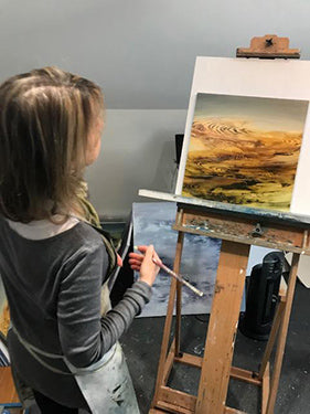 Deborah Weiss painting her landscape painting