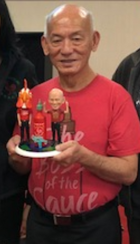 David Tran with his custom bobblehead (including a giant bottle of his Sriracha sauce) from Bobble For A Cause!