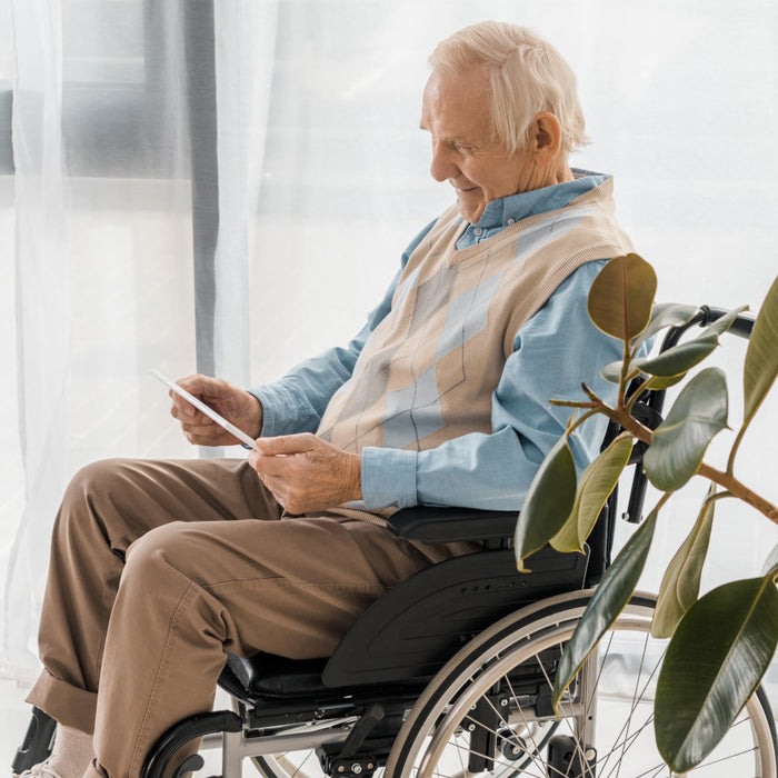 man in wheelchair holding tablet