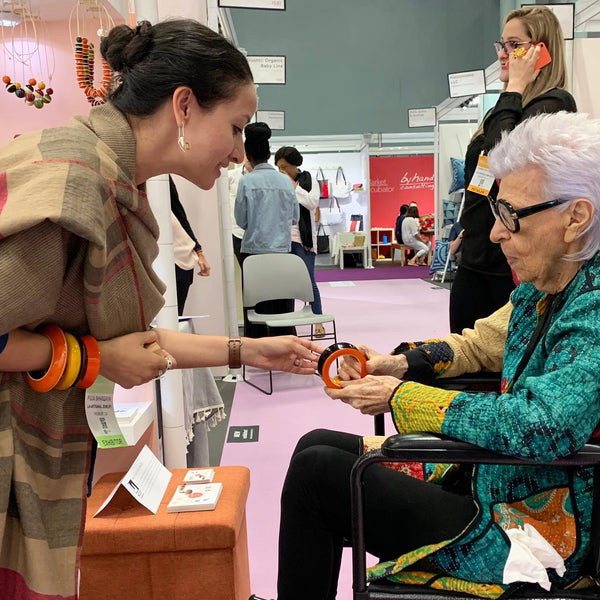 Iris Apfel at Lai booth at NY NOW 2019, with designer Puja Bhargava Kamath. Seen here wearing our Channapatna handcrafted lacquered wooden warrior dramatic bangle