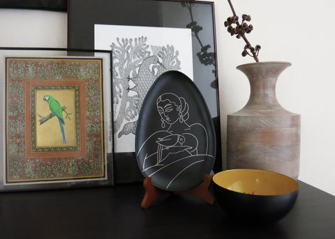 Decorative plates for home decor. Bidri metal and silver teardrop-shaped plate. Lady with a parrot. Design led, luxe, handmade home decor art objects. Handmade in India by Lai and Craft Stories