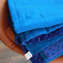 Laden Sie das Bild in den Galerie-Viewer, BLUE COTTON MINKY WEIGHTED BLANKET WITH COBALT MINKY BACKING ON THE ARMCHAIR
