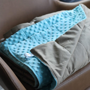 NUDE COTTON MINKY WEIGHTED BLANKET WITH LIGHT BLUE MINKY BACKING ON THE ARMCHAIR