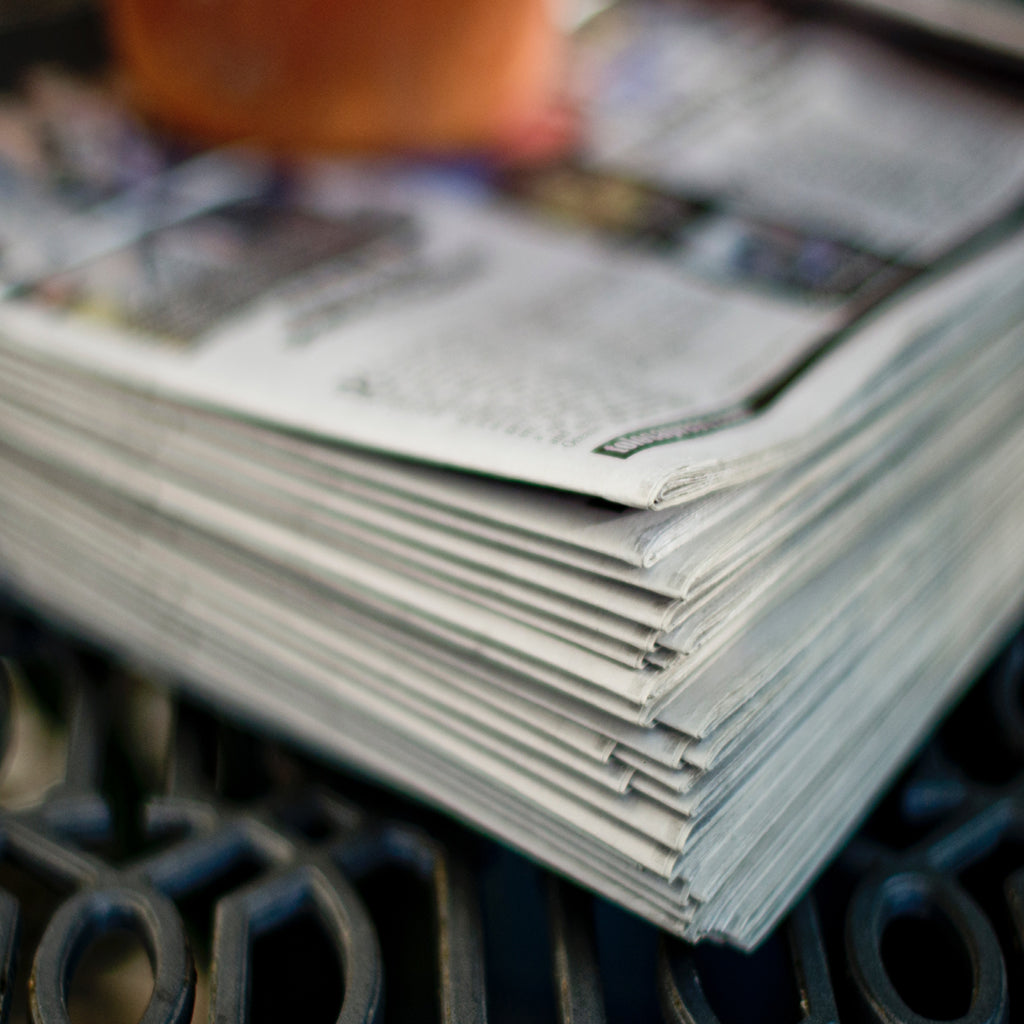 Tim Mossholder's photograph from Unsplash shows a stack of newspapers on a metal grate.