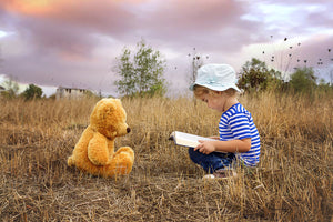 Girl reading to Teddy with beautiful sunset