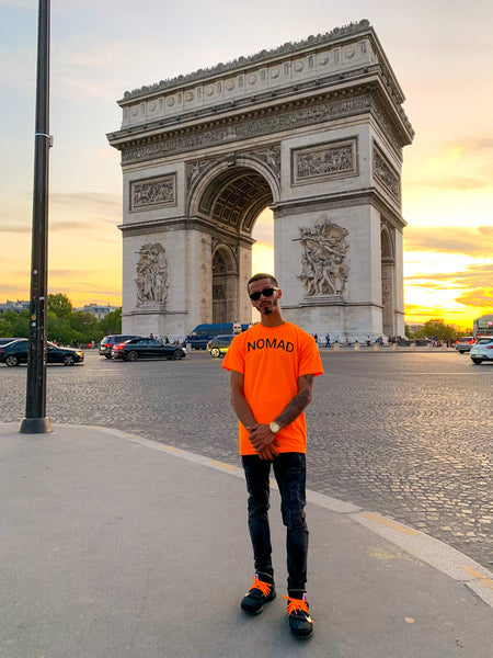 Nomad Creative Works Orange Front Printed T-Shirt With Off White x Nike Jeans in front of the Arc de Triomphe in Paris, France.