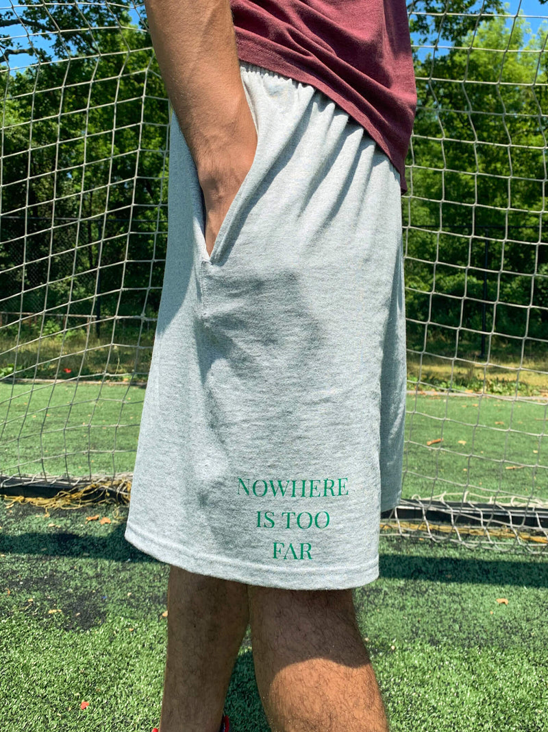 Modeled Left View Nomad Creative Works Grey Heather Shorts with Emerald Printing