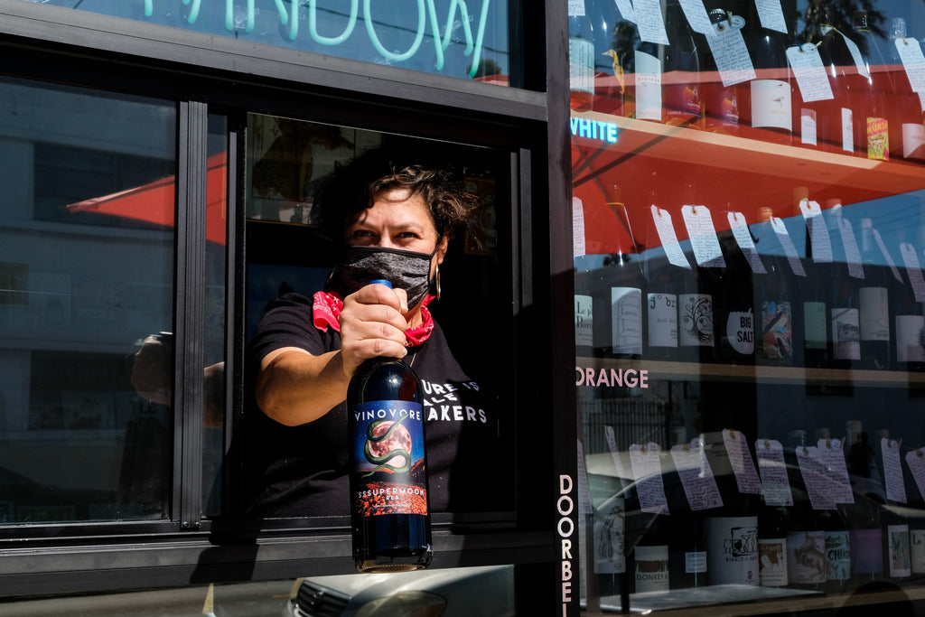 Coly Den Haan holding wine out of the wine window at Vinovore