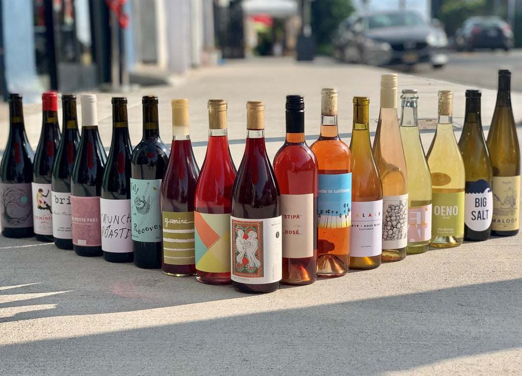A collection of Vinovore wines, lined up on the street