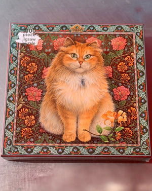 Square-box 1000-piece jigsaw puzzles from Flame Tree, featuring powerful and popular works of art. The Russian Princess, Blossomire is a pedigree Siberian Forest cat. This painting of her by Lesley Anne Ivory took many weeks to complete and Lesley commented that 'she was both a challenge and a joy to portray'.  Blossomire's crown can be seen at the top of the painting; it was inspired by honeysuckle and is set with emerald and jade for her eyes as well as rubies for her warmth.