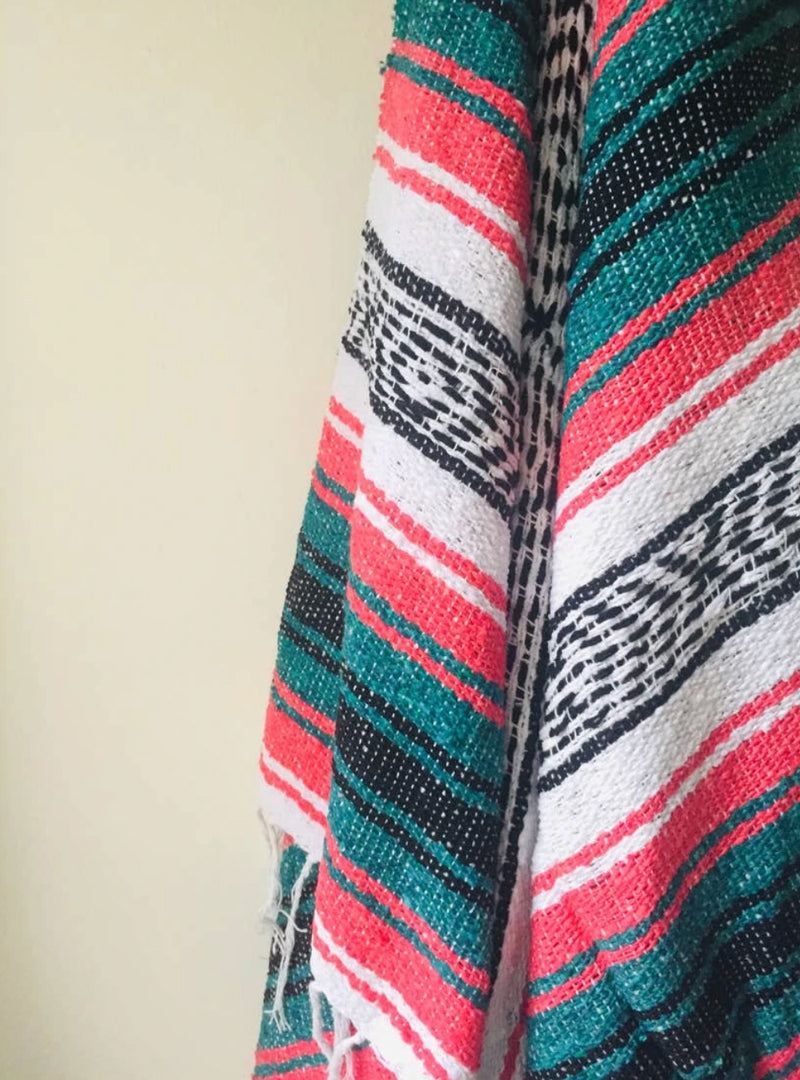 "Measure 74"" x 48"" Colors: Coral, Teal, Black & White Fringe detail on two ends Soft blend of cotton, acrylic and polyester Washes well in cold cycle and recommended to air dry Perfect as your favorite couch or bed throw, picnics, concerts, and the beach."