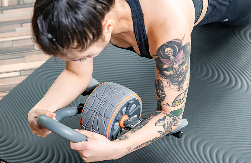 A woman doing abdominal workout using Dmoose ab roller