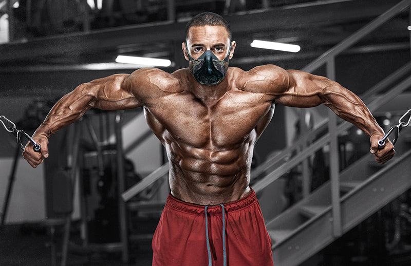 A bodybuilder doing exercise in gym while wearing  Gym Mask on his face