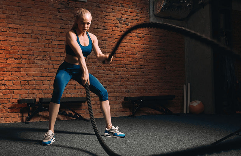 A woman doing workout to increase her stability while using DMOOSE fitness rope