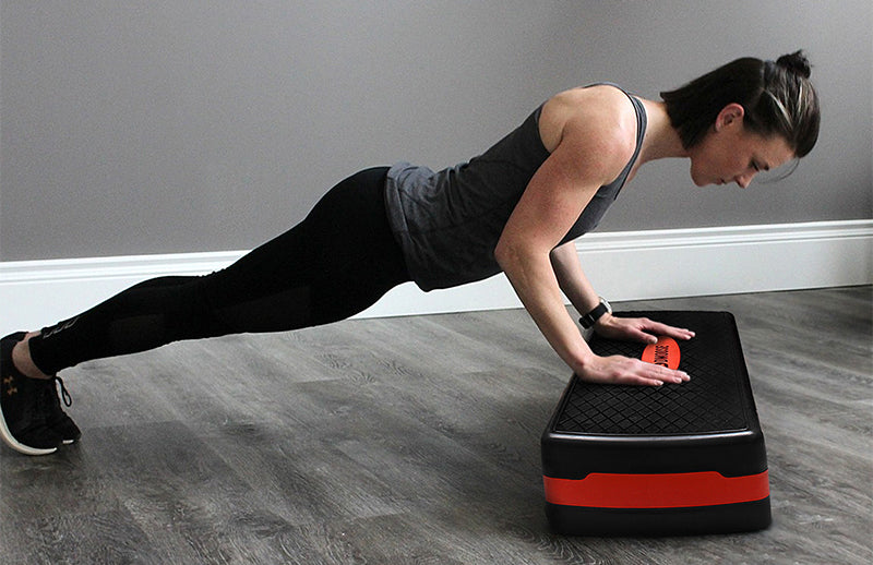 A woman doing push-ups by using  aerobic stepper to place hands