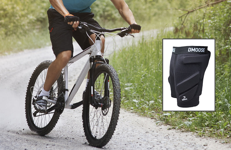 A man cycling while wearing DMOOSE padded shorts for cycling