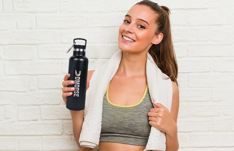 A woman showing DMOOSE stainless steel water bottle while holding it in her hand