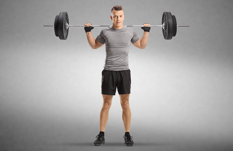 A strong man holding a weighted barbell behind his neck while wearing DMOOSE cross-training gloves